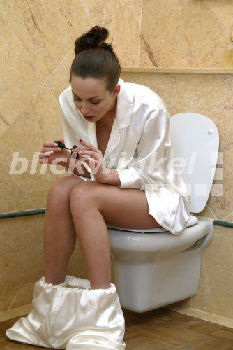 blickwinkel - Frau sitzt im Bad auf der Toilette, lackiert