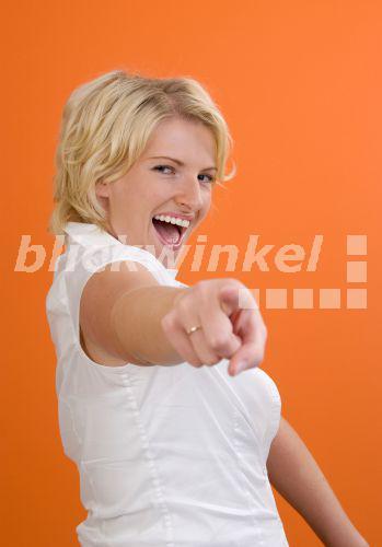 blickwinkel - lachende junge Frau zeigt mit dem Finger