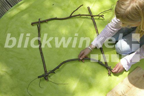 Blumenbild weben. Maedchen legt einen Rahmen aus Aesten, Serienbild 1 ...